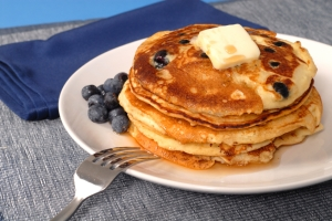 A stack of blueberry pancakes with maple syrup