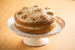 Beautifully presented Coffee and Walnut cake on a white cake stand